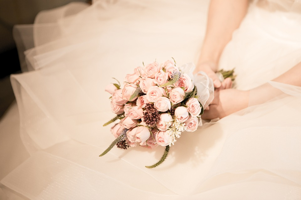 bride in wedding gown, holding flowers.