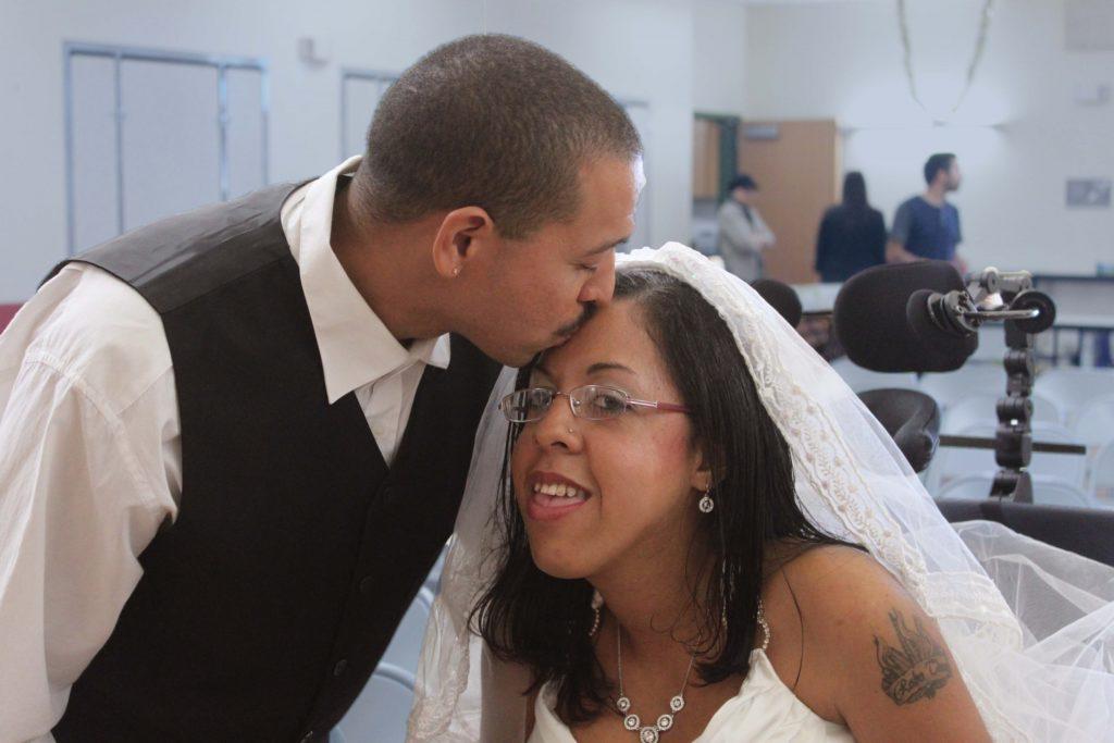 husband kissing bride's forehead.