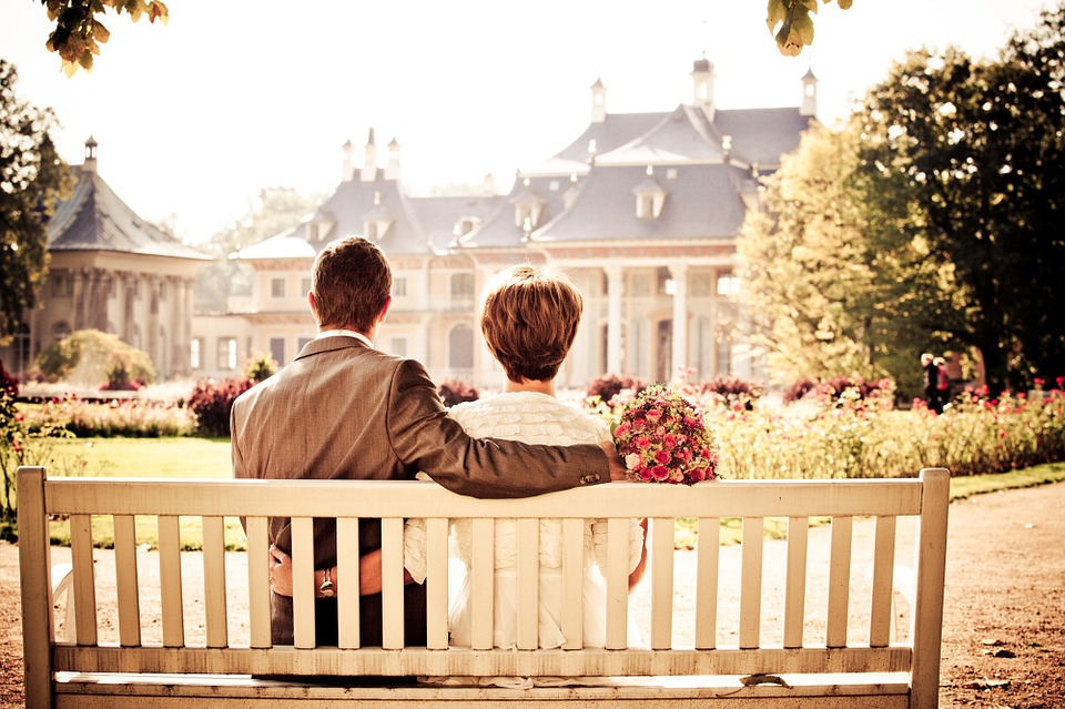 couple sitting on bench, facing church.