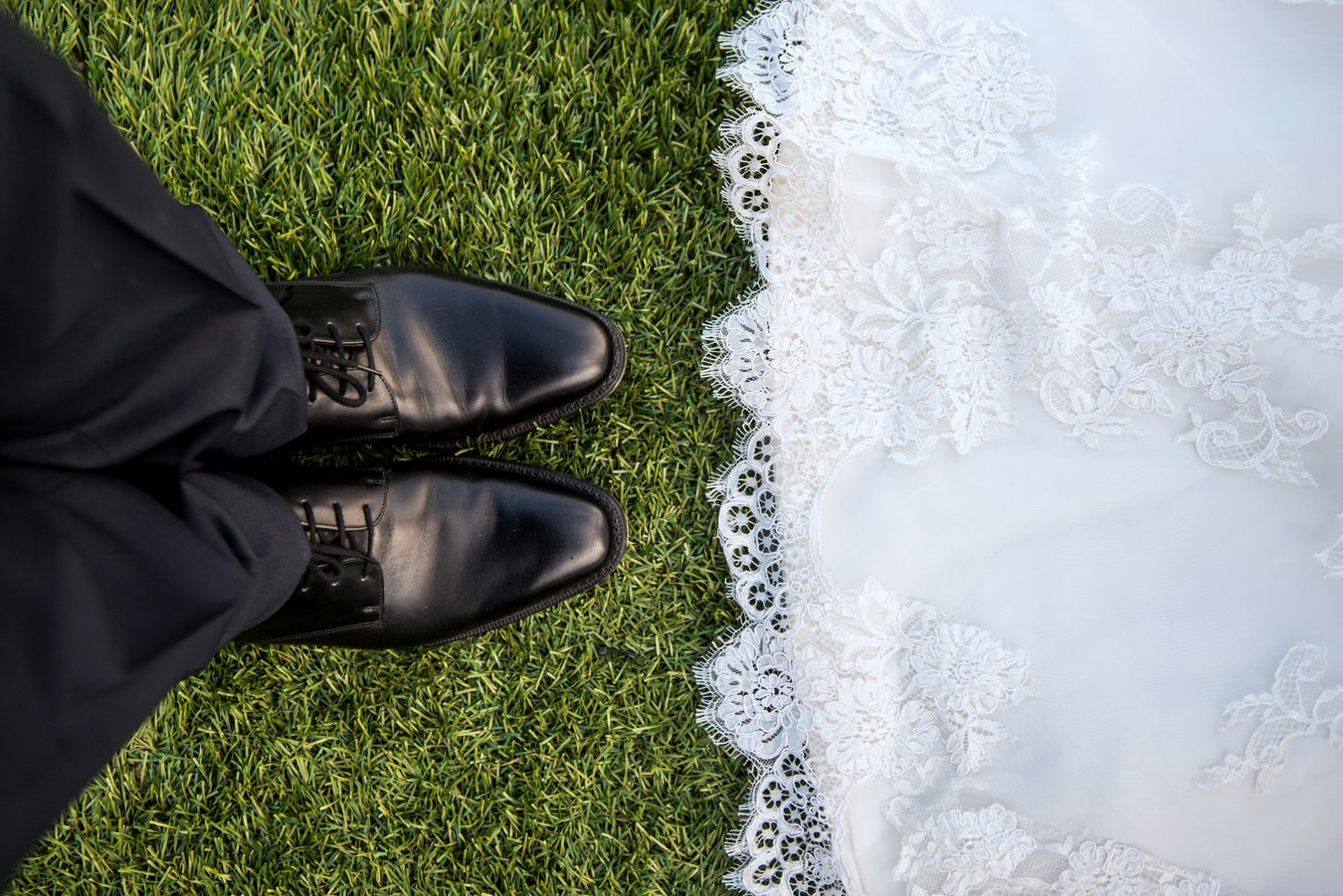 top shot of wedding dress and groom's shoes.