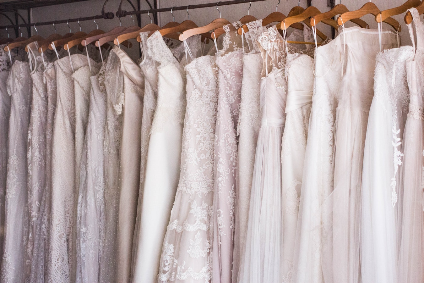 ros of wedding dresses on hangers.