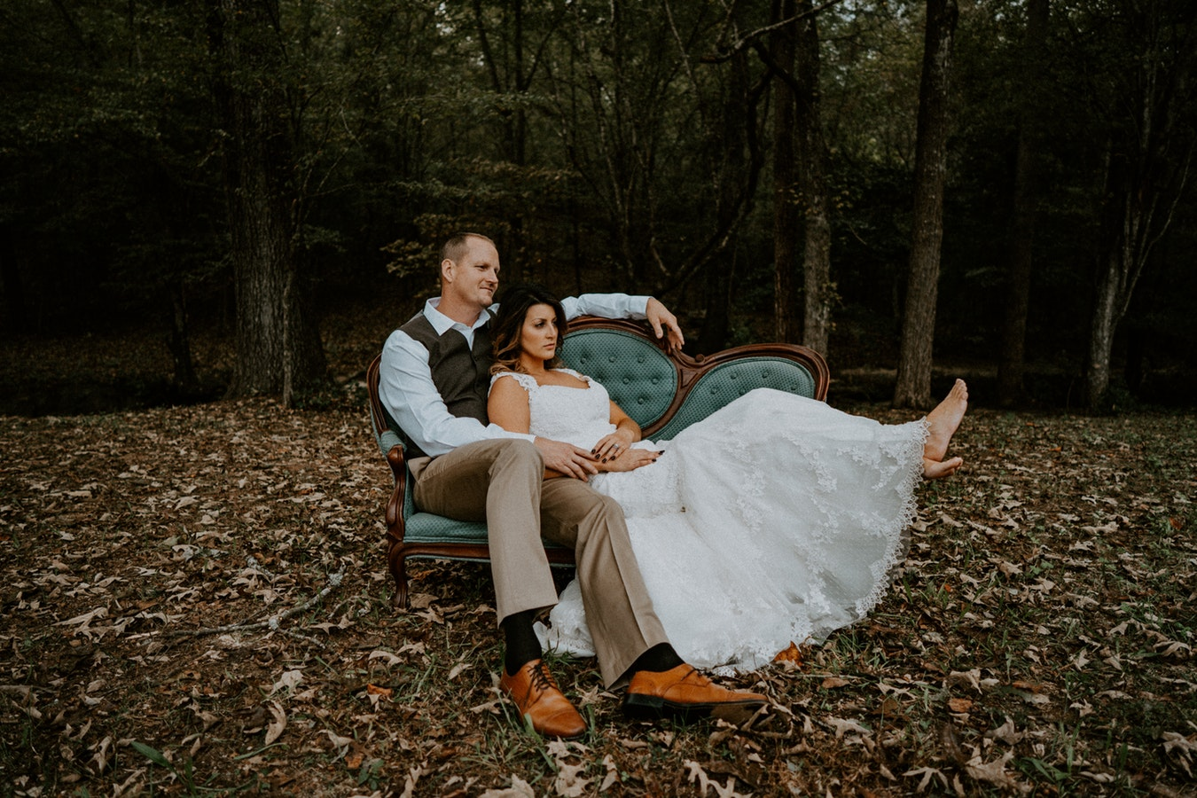 groom and bride sitting on couch in nature.