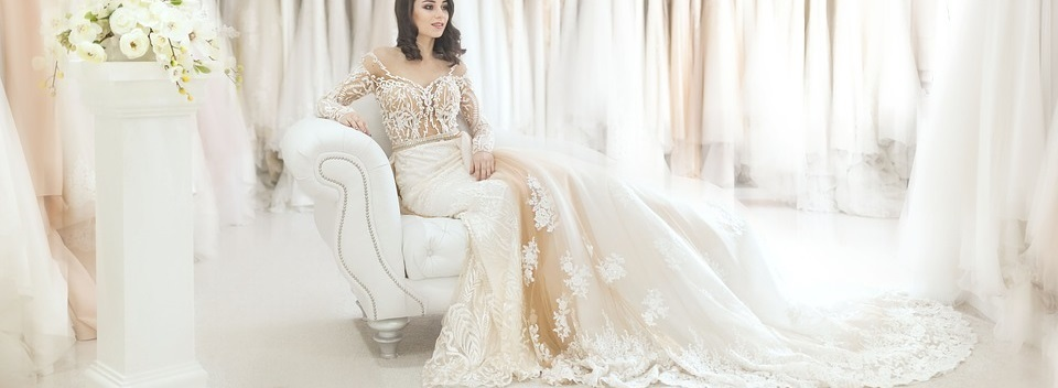bride sitting on a couch in a long wedding dress.