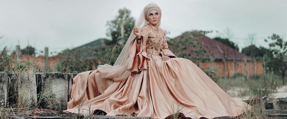 bride sitting in peach wedding dress.