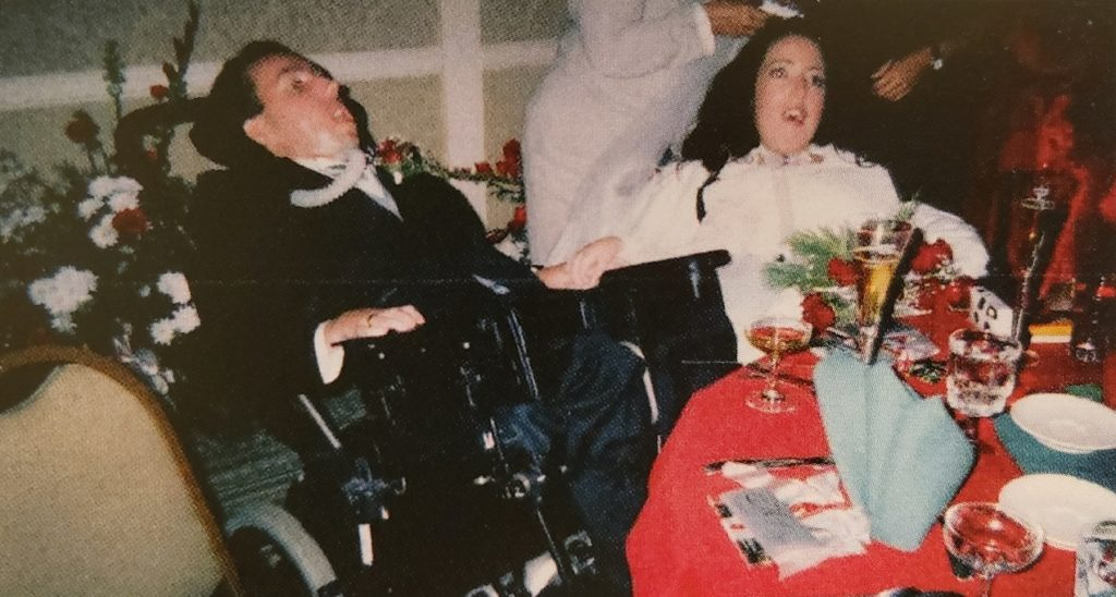 Bride and husband in wheelchair at wedding table.