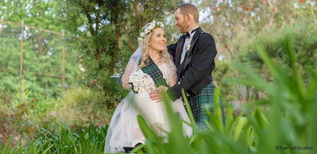 Bride in wheelchair with husband, in grass.